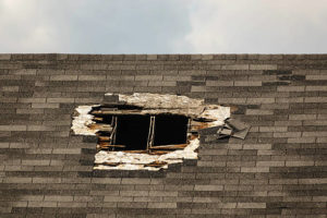 Large hole in shingled roof, for themes of security, insurance, repair